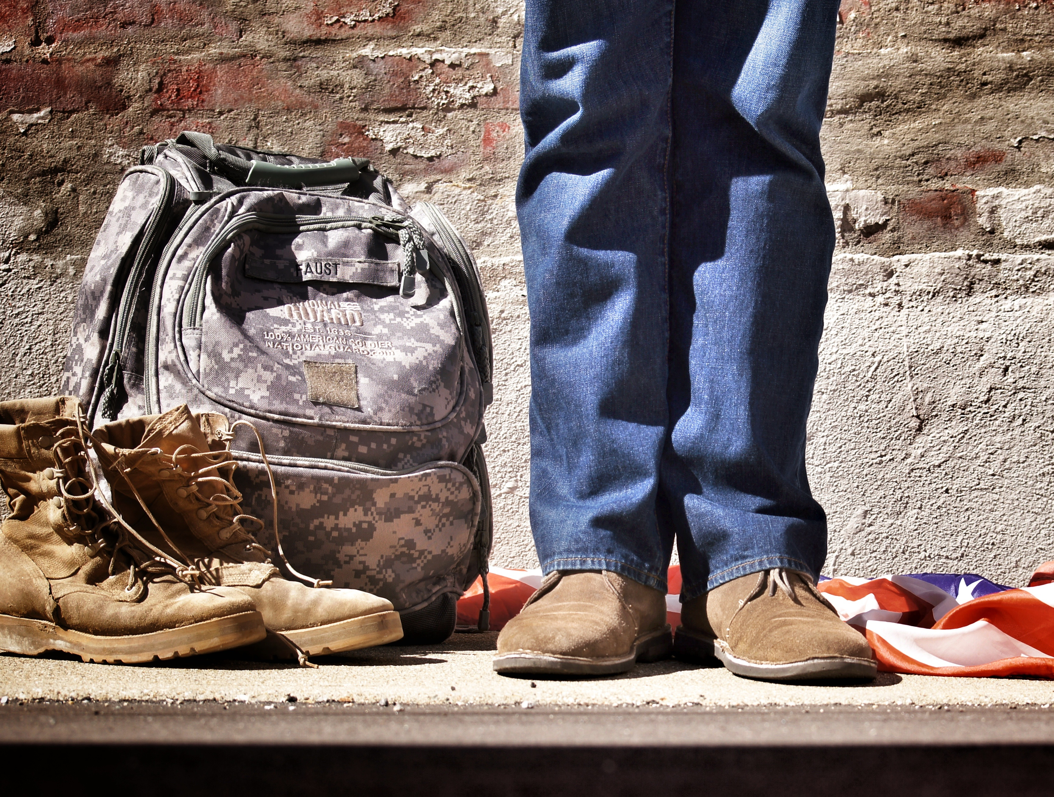 military backpack next to civilian-dressed legs -benjamin-faust